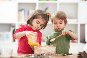 Two kids cooking at home.